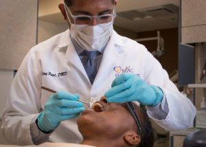 Dentist Dr. Vijay Patel of the Marana Dental Clinic treating dental patient.