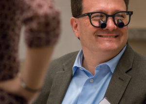 Endodontist dentist instructor smiles with loupes on