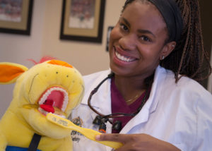 Surprise, Arizona dentist, Dr. Jessica Peterkin brushing stuffed animal's teeth