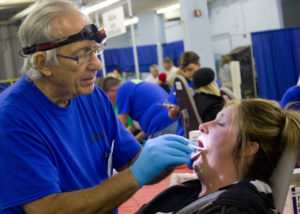 Dentist examining a patient at dental charity event
